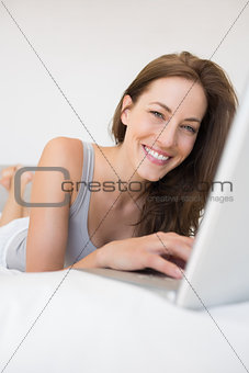 Portrait of relaxed woman using laptop in bed