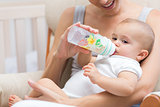 Mother feeding baby with milk bottle