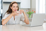 Thoughtful woman with coffee cup and laptop in kitchen