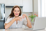 Smiling woman with coffee cup and laptop in kitchen