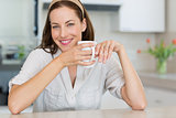 Smiling young woman with coffee cup in the kitchen