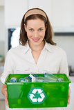 Smiling young woman carrying box with recycling symbol