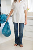 Low section of woman carrying garbage bag in kitchen