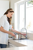 Side view of woman with vessel at washbasin in kitchen