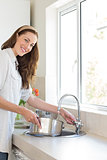 Smiling woman with vessel at washbasin in kitchen