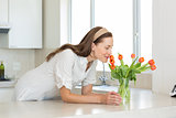 Smiling woman smelling flowers in kitchen