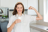 Happy woman flexing muscles while drinking water in kitchen
