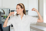 Woman flexing muscles while drinking milk in kitchen