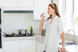 Side view of a woman drinking water in kitchen
