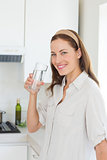 Portrait of a woman drinking water in kitchen