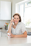 Smiling woman with coffee cup using landline phone in kitchen