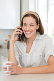 Smiling woman with coffee cup using mobile phone in kitchen