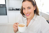 Portrait of a smiling woman with coffee cup in kitchen
