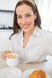 Smiling woman with coffee cup in kitchen