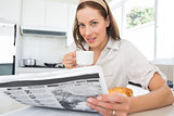 Smiling woman with coffee cup and newspaper in kitchen