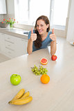 Smiling woman with fruits gesturing thumbs up in kitchen