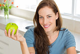 Smiling young woman holding apple in kitchen