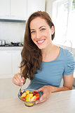 Smiling young woman with fruit salad in kitchen