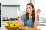 Woman with fruit bowl on counter in kitchen