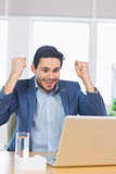 Businessman with clenched fists using laptop
