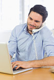 Businessman using laptop and telephone