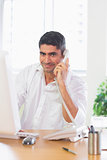 Businessman using landline phone and computer
