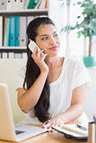 Businesswoman using mobile phone at desk