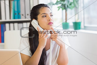 Thoughtful businesswoman using landline phone