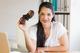 Businesswoman holding binoculars at desk