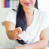 Midsection of businesswoman giving business card