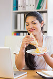 Businesswoman having sandwich while looking at laptop