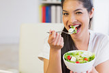 Happy businesswoman eating healthy salad