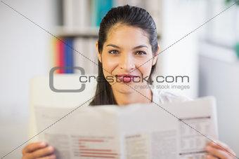 Portrait of businesswoman reading newspaper