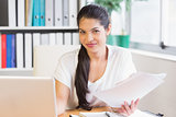 businesswoman holding papers at office desk