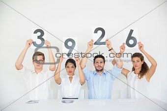 Business people holding score cards
