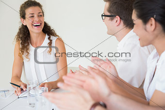 Business people applauding for businesswoman