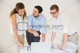 Business people discussing over laptop