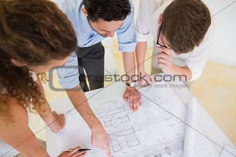 Business people studying blueprint