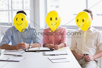 Business people holding balloons in front of face