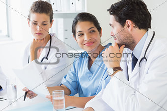 Doctors and nurse discussing over document