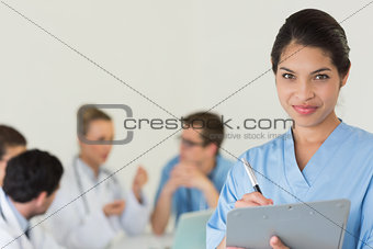Female nurse writing on clipboard