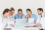 Doctors and nurses discussing over laptop