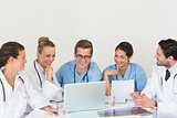 Medical team discussing over laptop