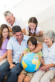 Multigeneration family looking at globe