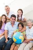 Smiling multigeneration family with globe