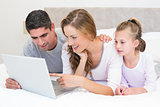 Family using laptop in bed