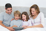 Family using digital tablet in bed