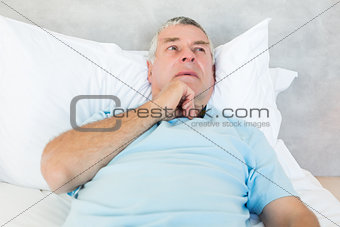 Thoughtful senior man lying in bed