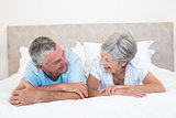 Senior couple looking at each other in bed