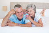 Loving senior couple lying in bed